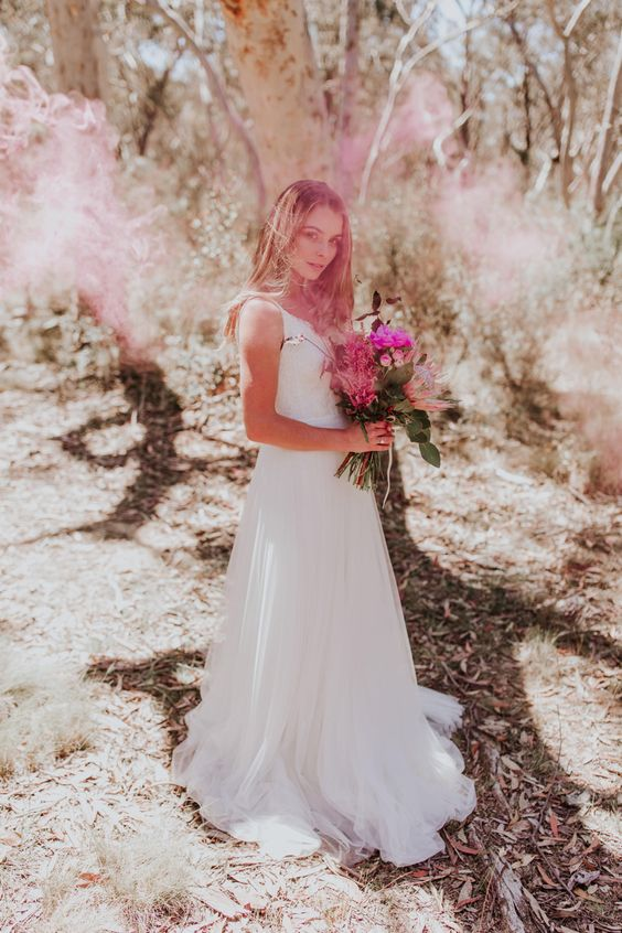 an airy bridal portrait with pink smoke in the woods is a very eye-catchy and delicate idea to try