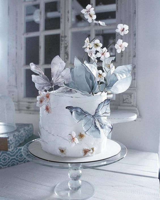 an artful wedding cake decorated with faux blooms, butterflies on sticks is a lovely and very tender idea of a wedding dessert