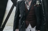 an edgy groom's look with black jeans, a printed shirt, a burgundy waistcoat, a black jacket and a printed tie plus a black hat