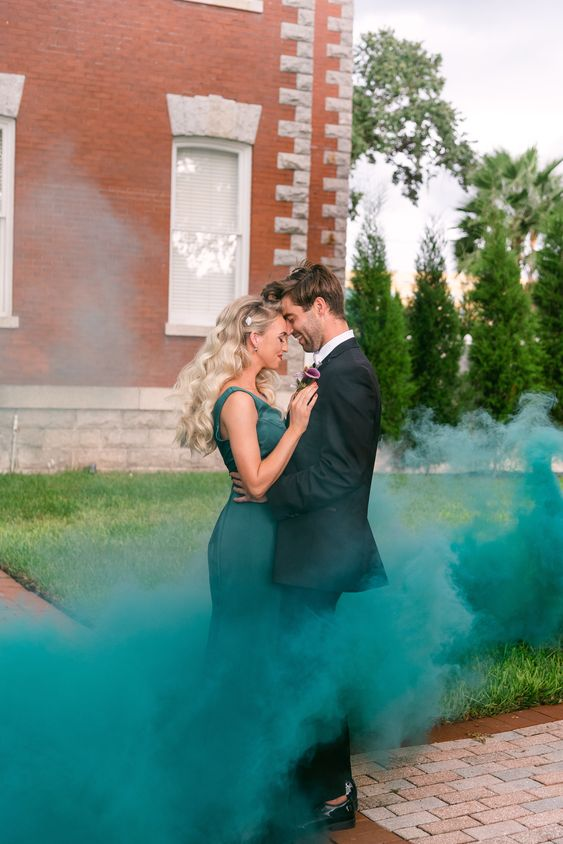 an elegant couple portrait accented with a green smoke bomb that echoes with the wedding dress