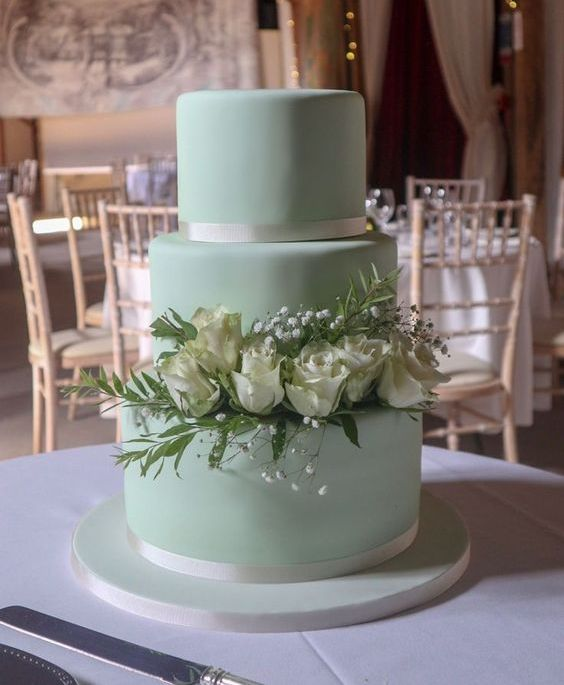 an elegant mint green wedding cake decorated with greenery, baby's breath and white roses