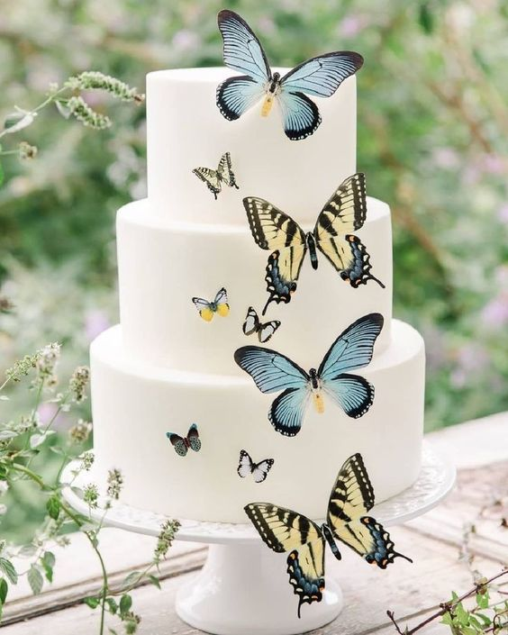 an elegant white wedding cake with yellow and blue butterflies is a chic and stylish idea that catches an eye