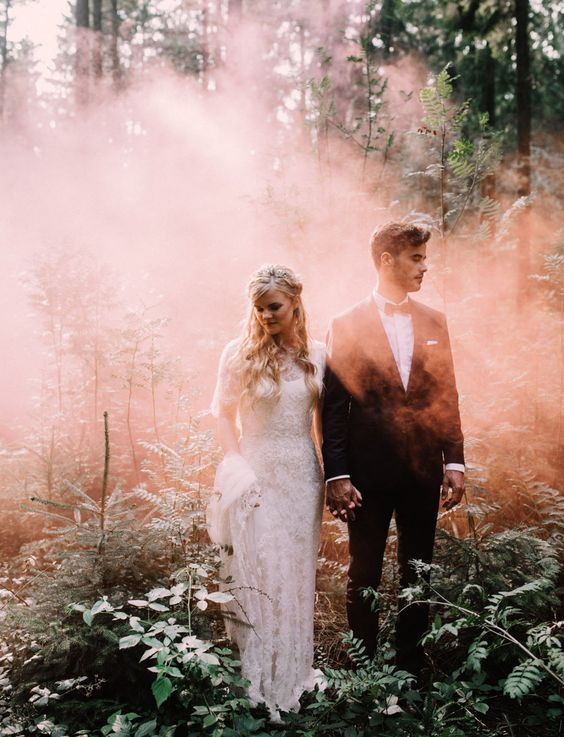 an ethereal wedding portrait in the woods, with pink smoke and sunligth coming through this smoke looks amazing