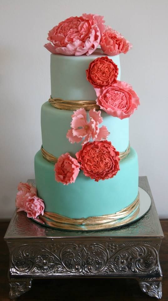 an ombre tiffany blue wedding cake decorated with gold and bright red and pink sugar flowers on top