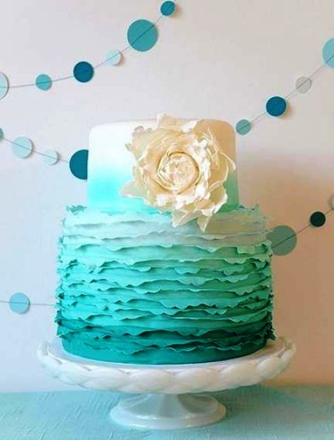 an ombre tiffany blue wedding cake with a textural tier and a large white sugar bloom