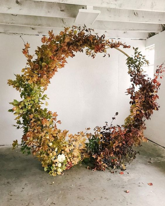 an oversized fall wedding wreath covered with leaves and dried foliage with an ombre effect is a fantastic idea for a rustic wedding