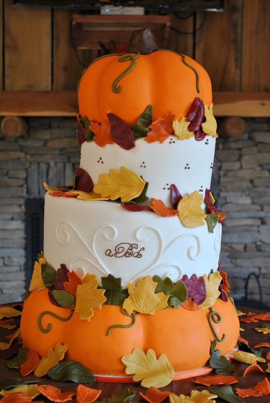 an oversized white buttercream and pumpkin wedding cake with sugar leaves is a fun idea for a fall rustic wedding