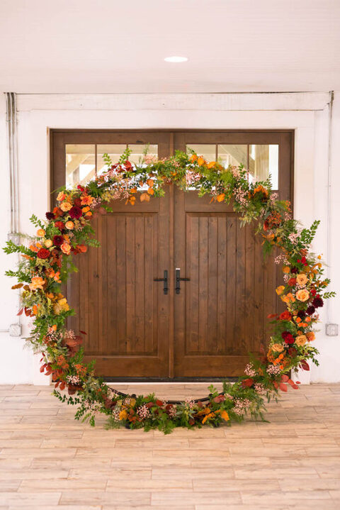 ann oversized fall wedding wreath that can be used as a wedding arch, covered with greenery, bold leaves and bright orange, deep red and burgundy blooms