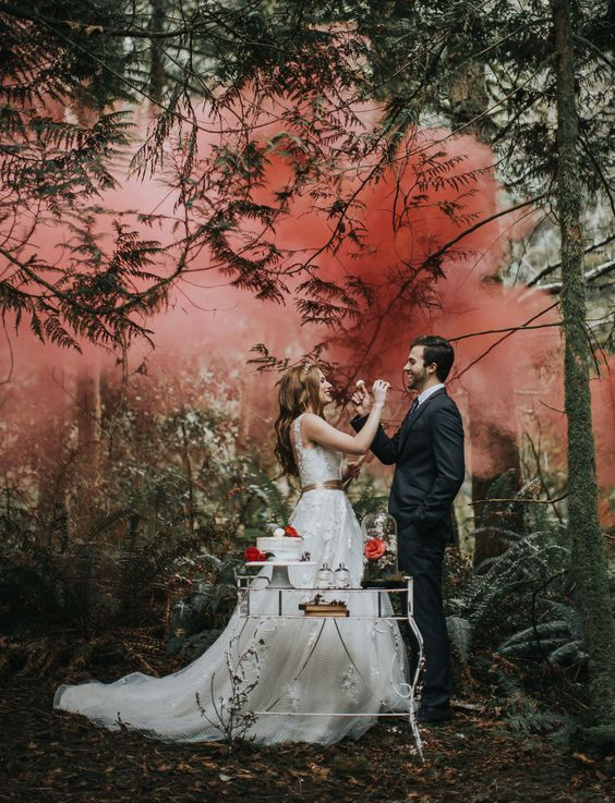 cake cutting made more special with red and pink smoke bombs right in the forest to accent the green space with color
