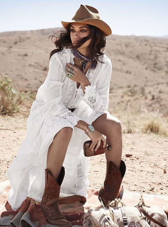 classic cowboy boots - cutout and patterned ones, with a boho lace wedding dress, a tan hat and statement jewelry make this bridal look very boho-like