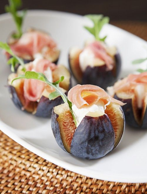 cut figs topped with cheese, proschiutto and arugula are a non traditional appetizer for the fall
