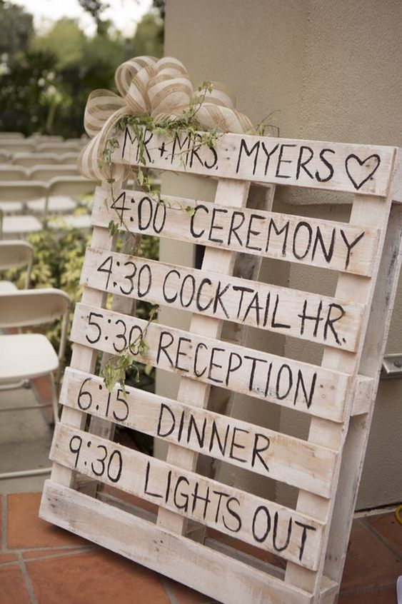 a DIY timeline wedding sign made of a whitewashed pallet with burlap bows and some greenery hanging down