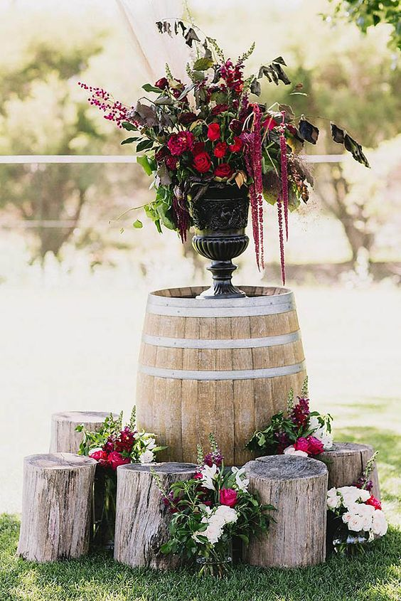 a barrel with an urn with bold and dark blooms and greenery, tree stumps around the barrel is a lovely decoration