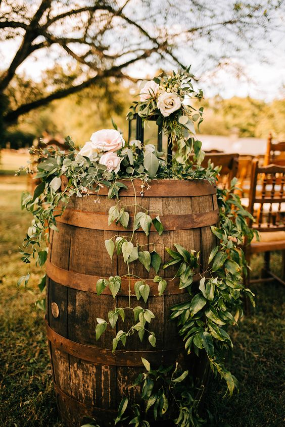 a barrel with vines, pastel blooms and a candle lantern is a lovely and easy to make rustic wedding decoration