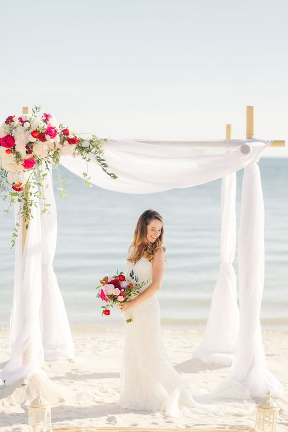 a beach bamboo wedding arch with white tulle and bright and neutral blooms to decorate a corner