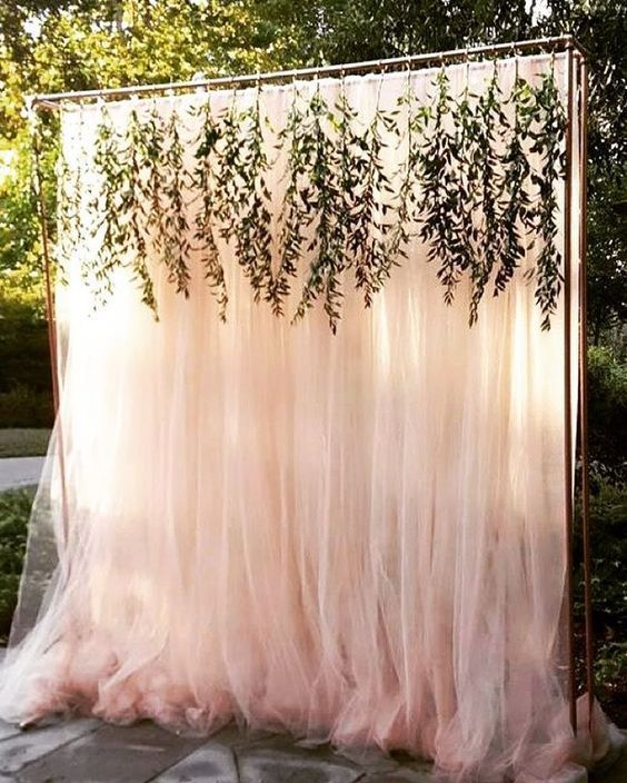 a beautiful blush tulle wedding backdrop with some greenery hanging down from copper piping