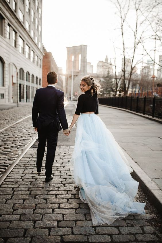 a black turtleneck crop top with short sleeves and a powder blue tulle skirt with a train is a bold modenr bridal look