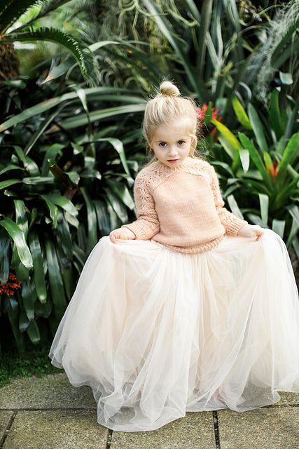 a blush sweater, a white tulle skirt and a top knot for a casual and simple winter flower girl look