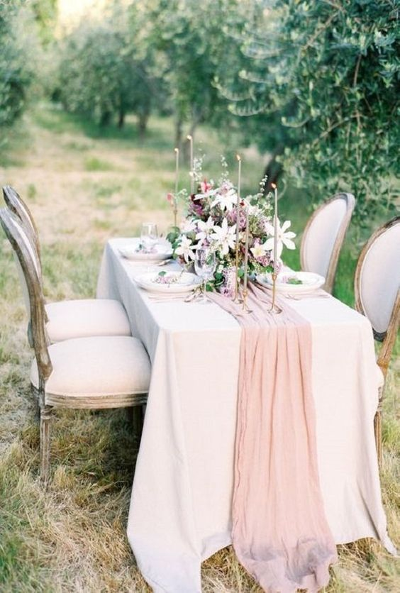 a blush tulle table runner adds a touch of pastel to this beautiful wedding al-fresco dinner