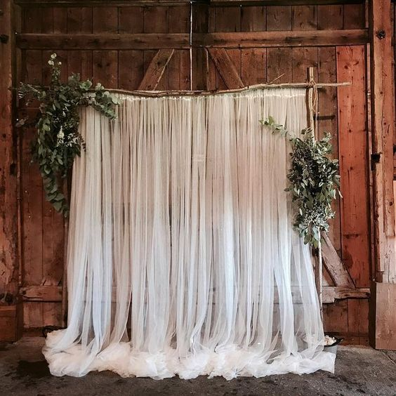 a branch, tulle curtains and greenery wedding backdrop is a cozy rustic piece for wedding decor