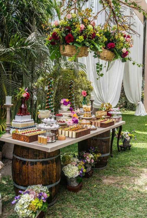 a bright tropical wedding dessert bar with barrels and a tabletop, fresh desserts and cakes of various kinds and bright blooms in baskets
