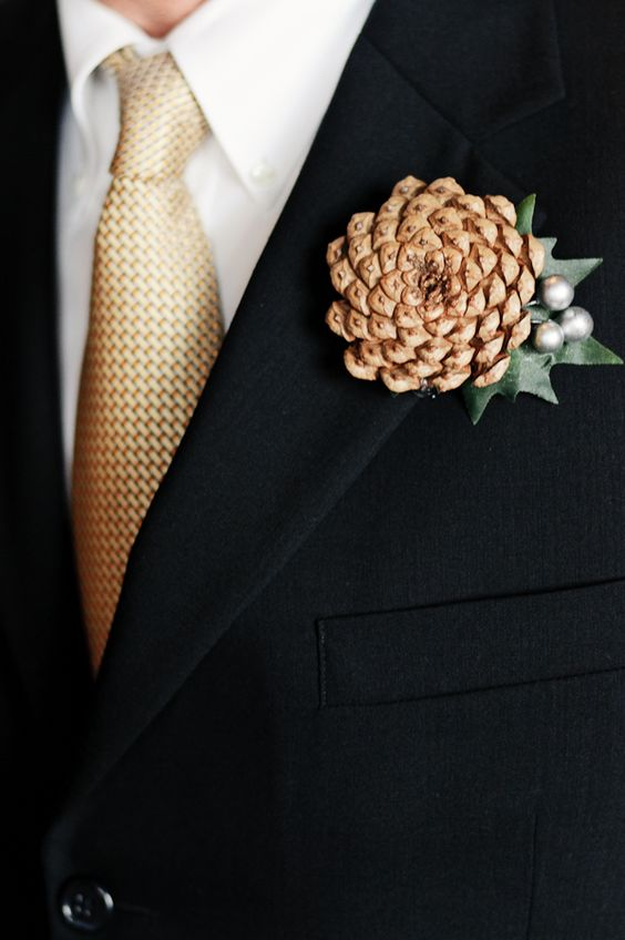 a chic pinecone, leaf and silver berries wedding boutonniere is a refined accent for a modern winter groom