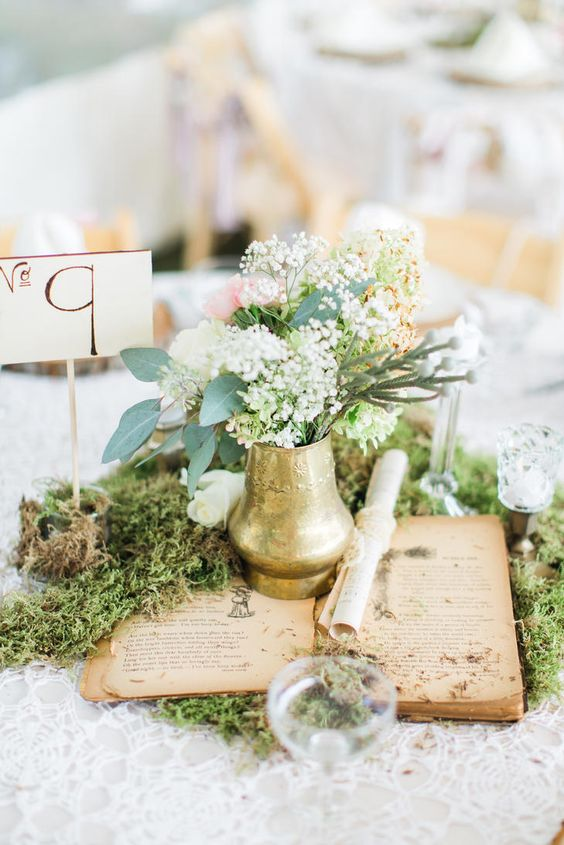 a chic vintage inspired wedding centerpiece with moss, an open book, a gilded vase and blooms plus a table number