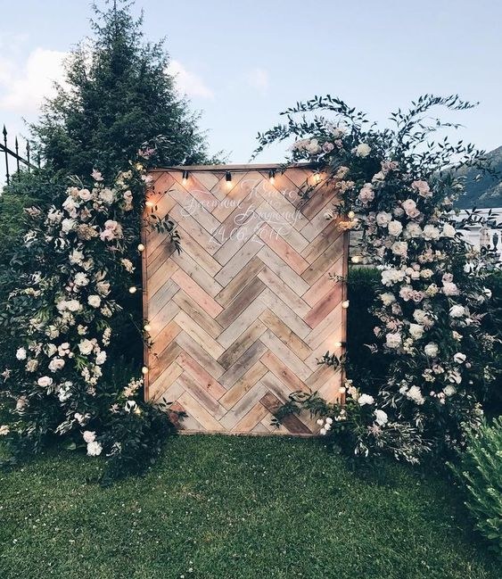 a chic wedding backdrop built of pallet wood clad with a herringbone pattern, lights and lush florals and greenery around