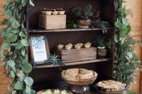 a chic wedding pie bar decorated with lots of greenery, succulents and air plants, various pies and mini cupcakes