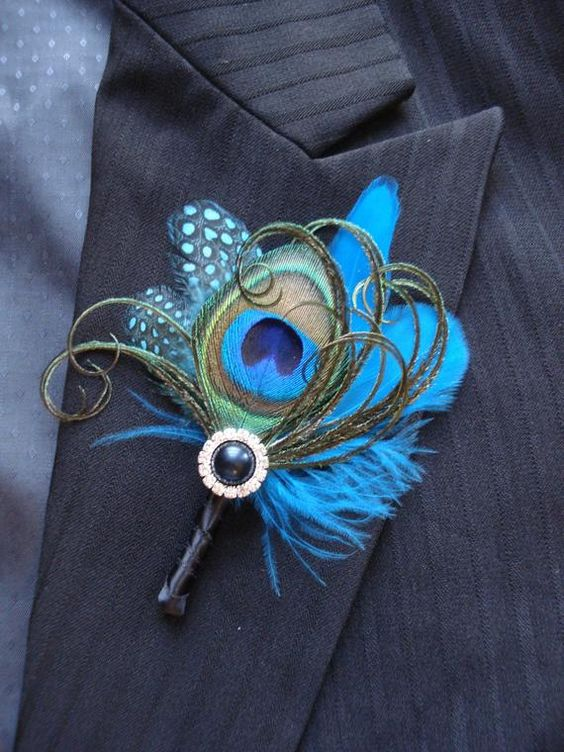 a colorful wedding boutonniere of bright feathers, a button and some yarn is a fun and cool piece