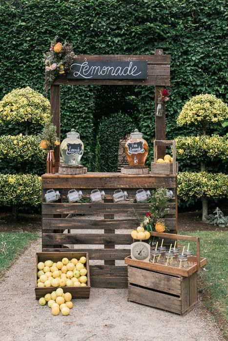 a cozy rustic drink bar of dark stained pallets, with lemons in crates and mason jars