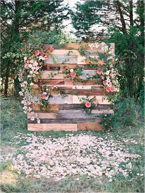 a cute pallet wedding backdrop with lush blooms and greenery plus petals all around looks very romantic