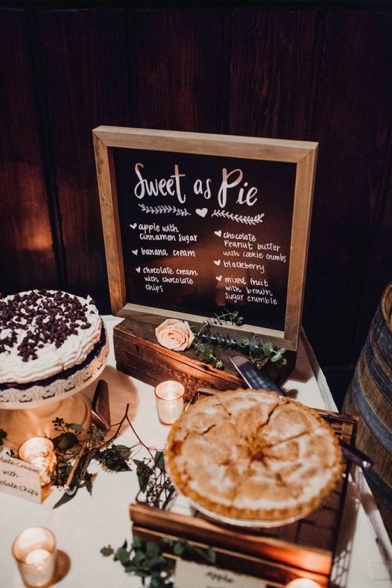 a cute rustic pie bar with greenery, blush roses, candles, a chalkboard sign in a frame and some pies on stands