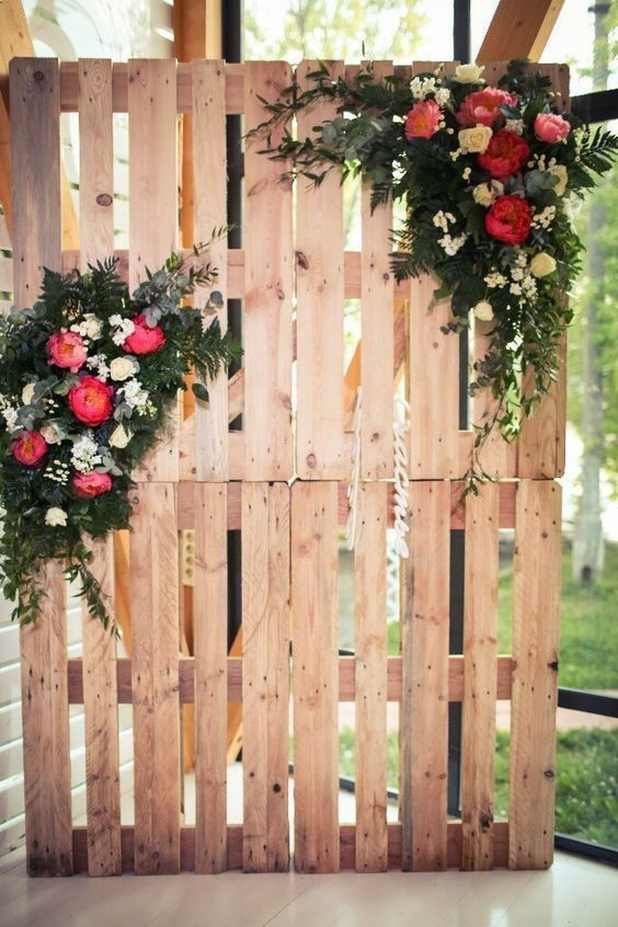 a cute rustic wedding ceremony or sweetheart table backdrop made of pallets and lush florals and greenery