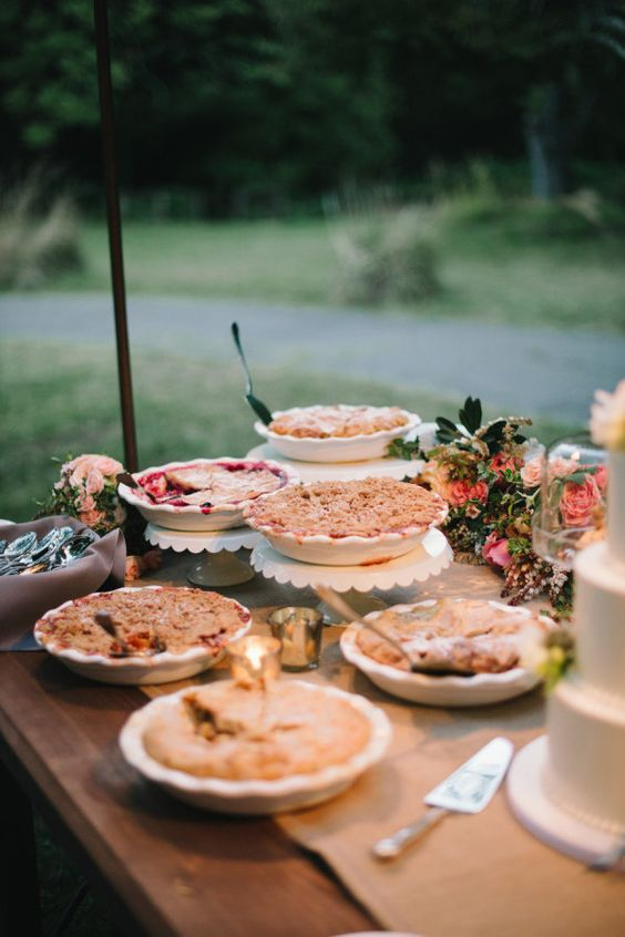 a cute summer wedding pie bar with pink blooms and greenery and pies on lovely stands or in plates is a cool idea to try