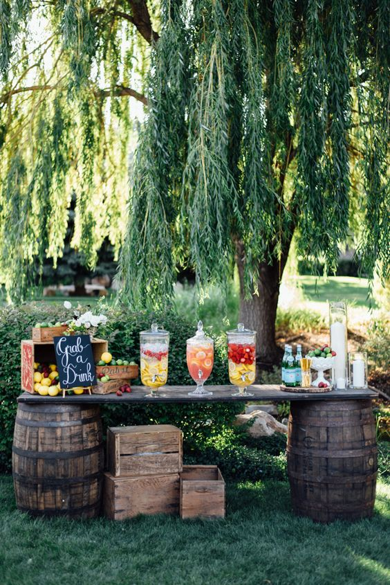 a drink bar based on two barrels and with a countertop, with lots of lemonades, fruits, drinks is a lovely idea for a rustic wedding