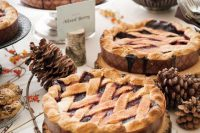a fall wedding pie bar done with wooden slices as pie stands, bold blooms and berries and pinecones is a very cool and chic idea