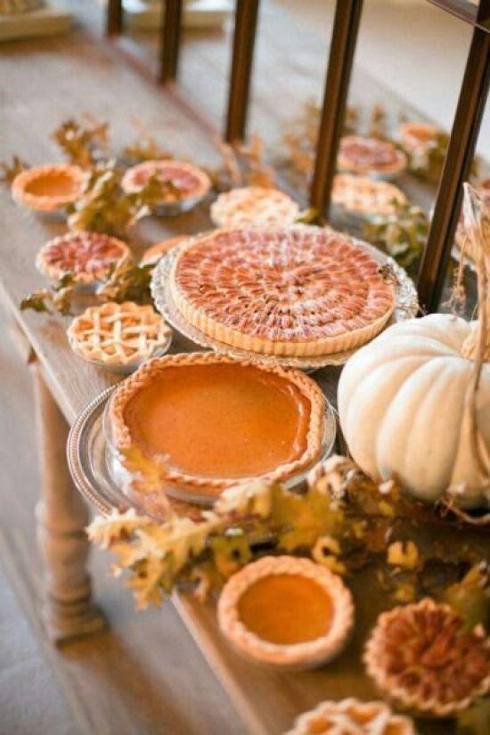 a fall wedding pie bar with dried leaves, pumpkins and some delicious fall inspired pies