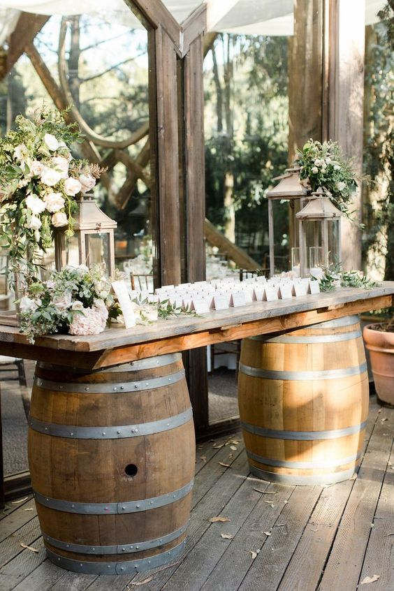 a farmhouse wedding gift table of barrels and a tabletop, lush florals and greenery and candle lanterns is cool