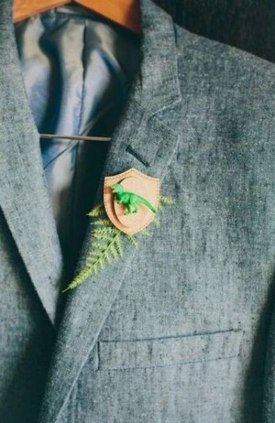 a funny wedding boutonniere of fern, a leather badge and a green dinosaur is a bright and cool idea to go for