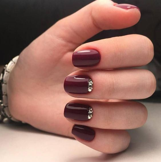 a glossy burgundy manicure with shiny gold embellishments is a lovely refined option to rock