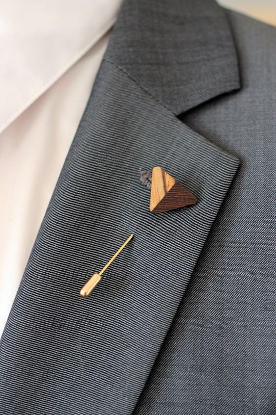 a gold and wood burnt arrow is a cool accessory for a boho-inspired groom's look