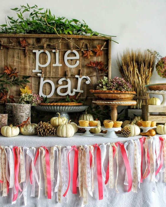 a gorgeous fall wedding pie bar with a colorful tassel garland, pinecones, white pumpkins, greenery, dried leaves and wheat