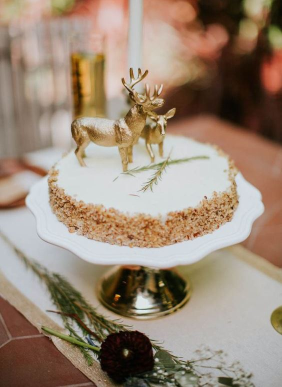 a krispie rice weddig cake with a creamy top, herbs and chic gold deer toppers for a woodland wedding