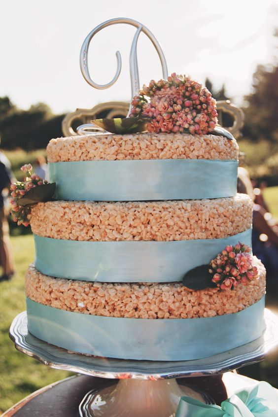 a krispie rice wedding cake with blue ribbons, pink blooms and foliage and a monogram on top