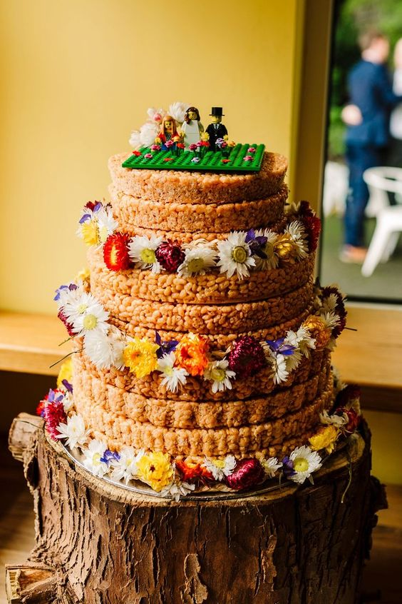 a krispie rice wedding cake with colorful blooms and a fun LEGO topper for a whimsy wedding