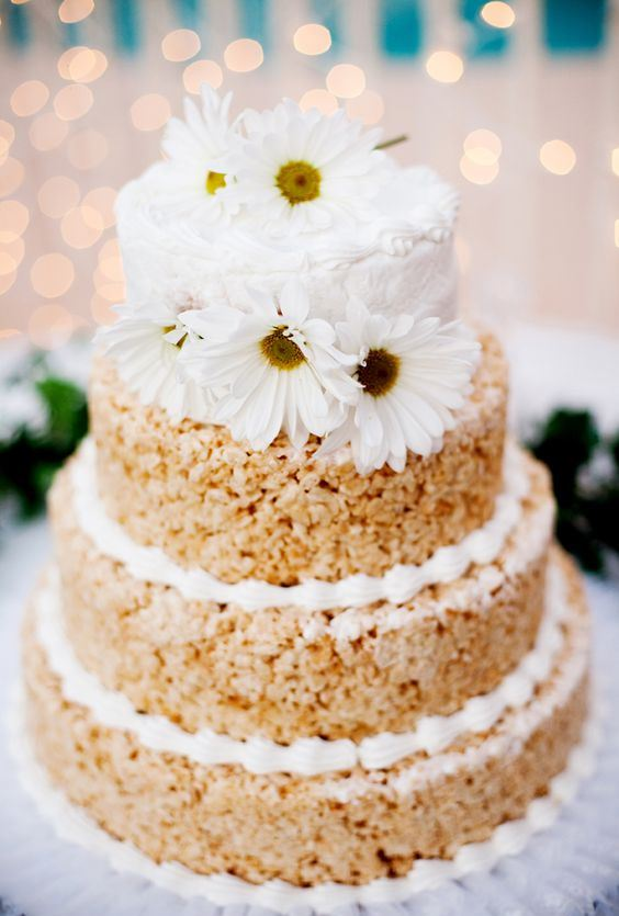 a krispie rice wedding cake with cream, a buttercream tier and white blooms on top for a rustic wedding
