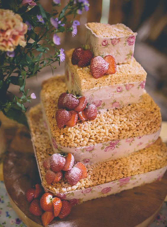 a krispie rice wedding cake with floral ribbons and strawberries on top for a rustic wedding