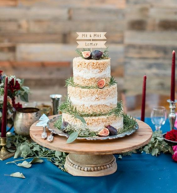a krispie rice wedding cake with fresh figs and greenery plus a cute wooden topper is a chic rustic piece