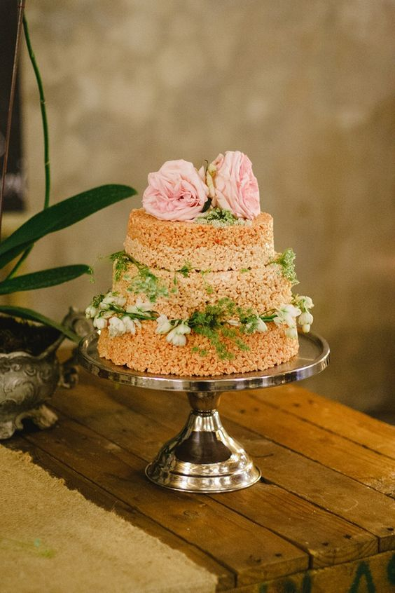 a krispie rice wedding cake with greenery, white and pink blooms is a stylish and timeless idea